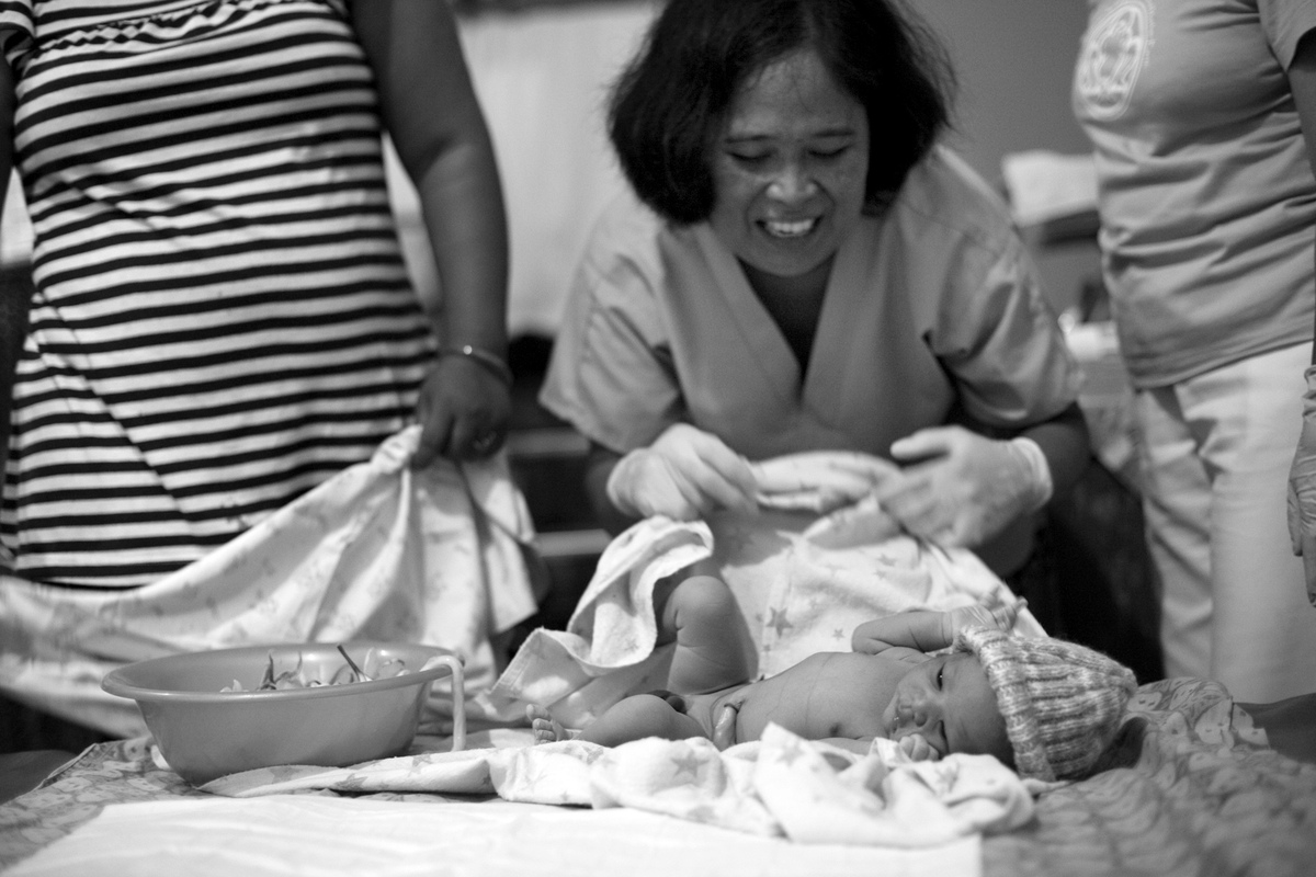 Virginie Noel Photography - The midwives cheerfully wrap up the new arrival.
