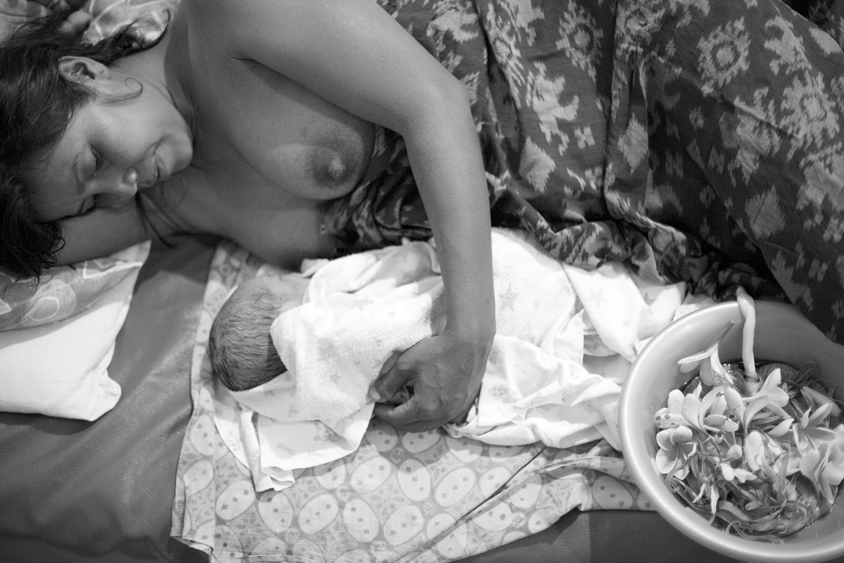 Virginie Noel Photography - Mother and baby. The placenta is treated with reverence in Bali. Later, accompanied by the appropriate rituals and ceremonies, it will be buried at a designated place in the family compound. This will be the babys home, his anchor in this world.