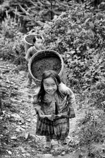 face of vietnam - Child labour with a smile A child carrying buckets of soil up a steep hill but with a smile