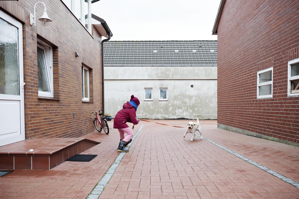 Fotografin Hamburg Reportage Portrait Reise Editorial Corporate Werbung Photography - After school, Kaya is greeted on her parent's farm by their dog Nala