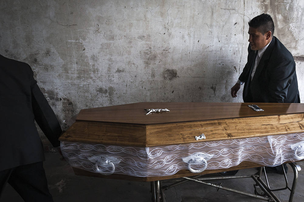 nicolascarvalhoochoa - The chofers, Darío Leguizamón (left) and Pablo Noel (right) move together the coffin of a deceased man to the visitation room of the funeral home.