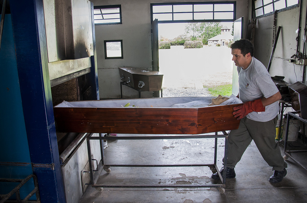 nicolascarvalhoochoa - Th creamator Fernando Moreno place the coffin of an old woman in one of the ovens of a private cementery in the province of Buenos Aires.