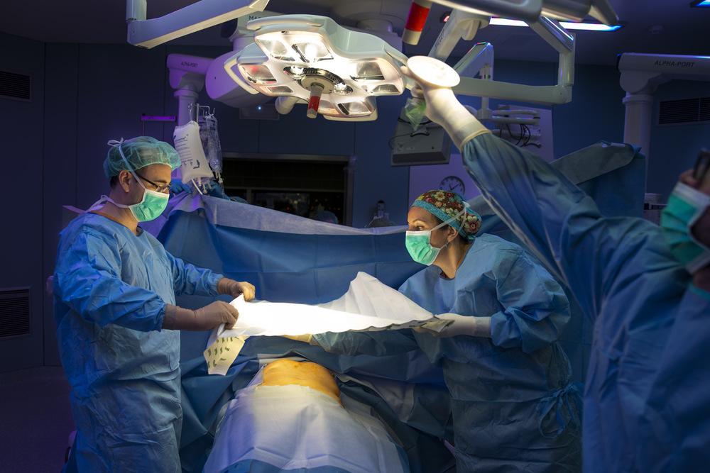 nicolascarvalhoochoa - Los cirujanos urólogos Jorge Ropero y Marta Allué cubren el cuerpo de un donante de riñones de edad mayor que se encontraba en la Unidad de Curas Intensivas con un daño neurológico irreversible en la Unidad de Curas Intensivas. Cuando pacientes cuentan con un nivel de detrimento irrecuperable se consulta a las familias la posibilidad de donación de órganos a través del proceso conocido como asistolia controlada, momento en que se detiene la ventilación que le permite estar aún con vida.