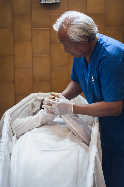 nicolascarvalhoochoa - Osvaldo Ferrari prepares a body before a wake at the funeral home. Osvaldo is responsable to bring the bodies from the morgues, hospitals or houses and then arranges them for the visitation.