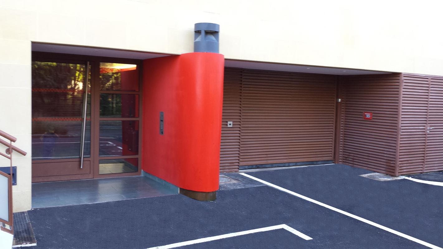 Architecte Marseille - Agence Elbaz Architecture à Marseille (13007) - Le hall jouxte l'entrée du parking. Nous l'avons ponctué d'un phare rouge. Les éléments techniques, accès sous-sol piétons, voitures, la chaufferie et les coffrets gaz, électricité, sont tous intégrés dans un parement en ventelles couleur rouille.