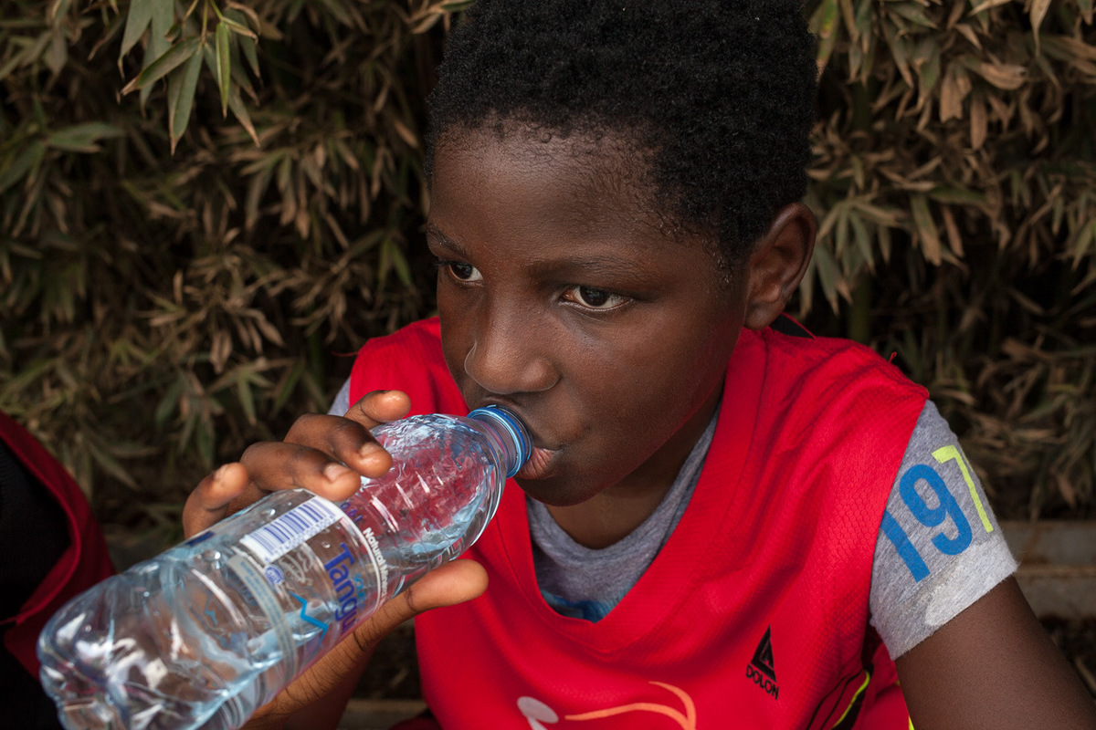 Adrienne Surprenant - Young player drinking water on a bench during a championship at Club Noah, Yaonde.