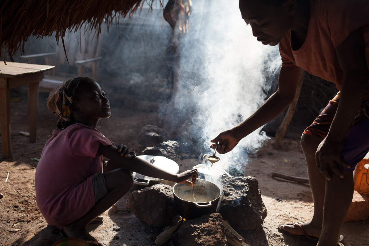 Adrienne Surprenant - A young girl prepares food for IDPs, some of whom are living between the houses of villagers.