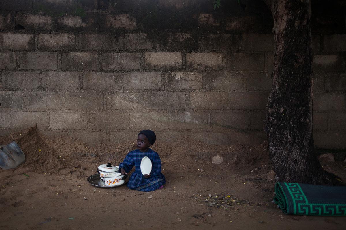 Adrienne Surprenant - 11 août 2017. Mokolo, Extrême-Nord, Cameroun. Une jeune fille est assise à côtés de plats, un peu à lécart dun mariage matinal.