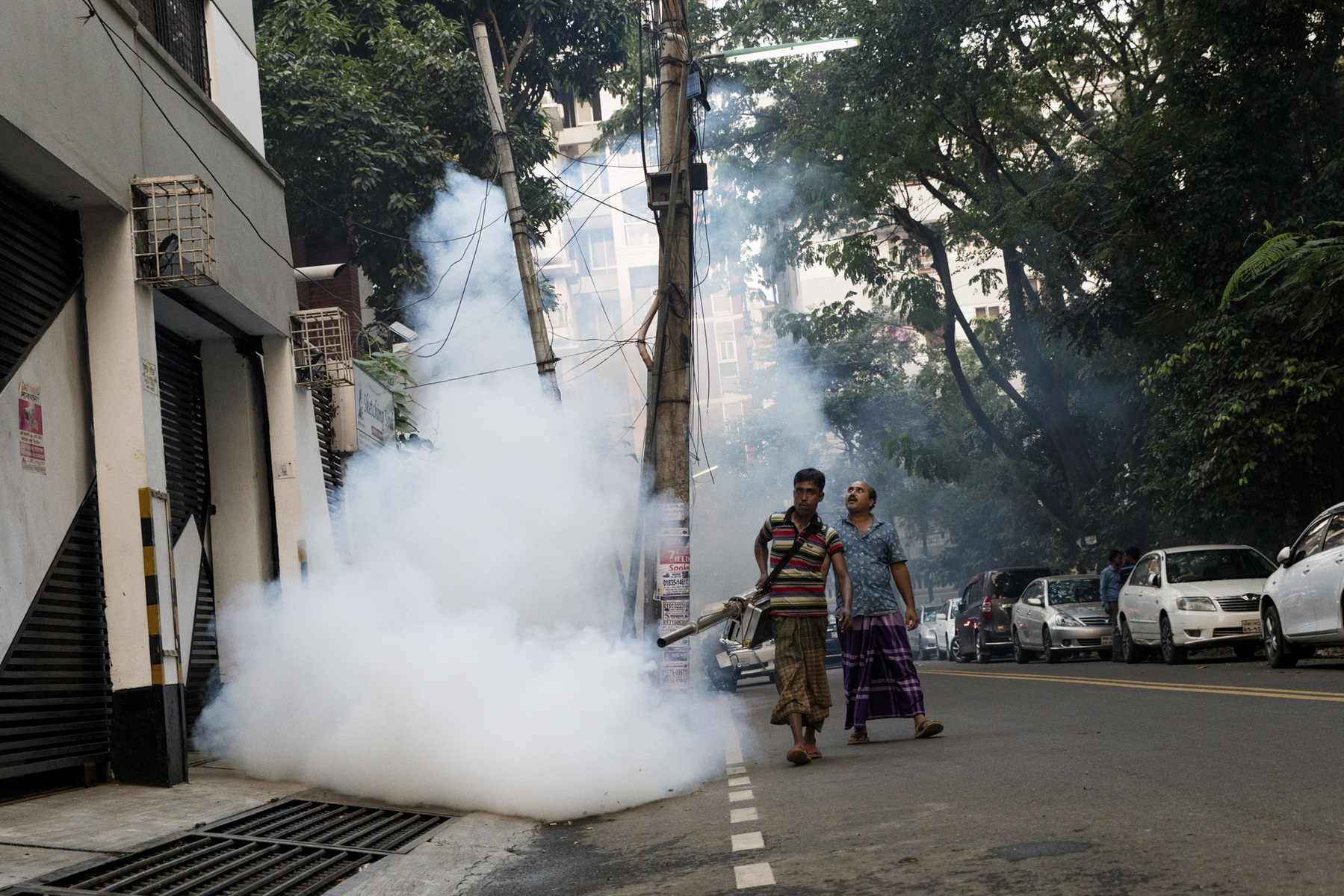 "Adrienne Surprenant - 24/10/2018, Uttara, Bangladesh— A man paid by the city corporation sprays the streets of Uttara, a ""model town"" in the North suburbs of Dhaka that boomed in the past 20 years. High middle-class neighborhoods are sprayed more often than the poorer areas of the capital but the residents seem unsure of the spraying's regularity: some say it is done daily, others once a month."