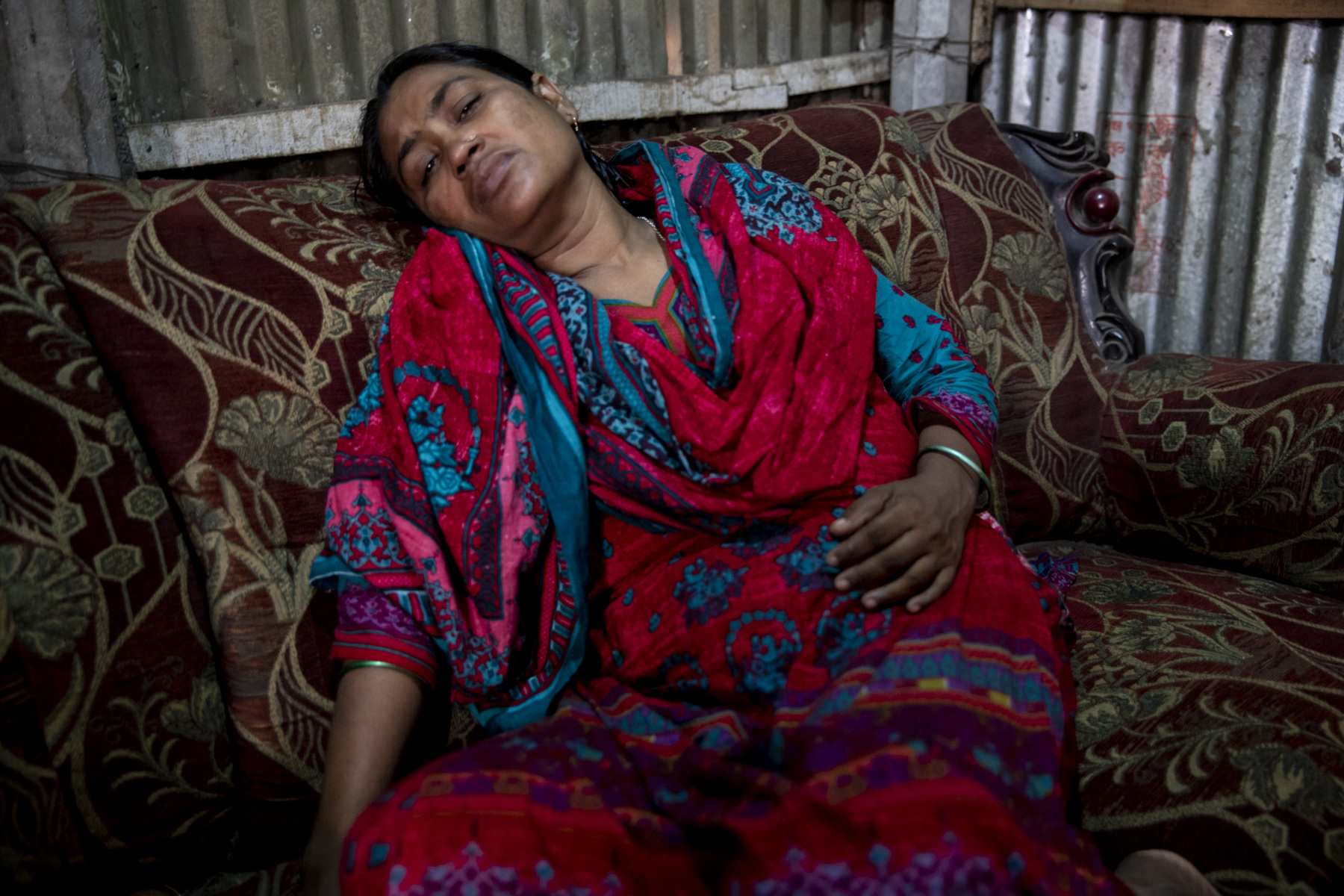 Adrienne Surprenant - 01/11/2018, Dhaka, Bangladesh—Meena Begum, Marufs mother, cries on her sofa.