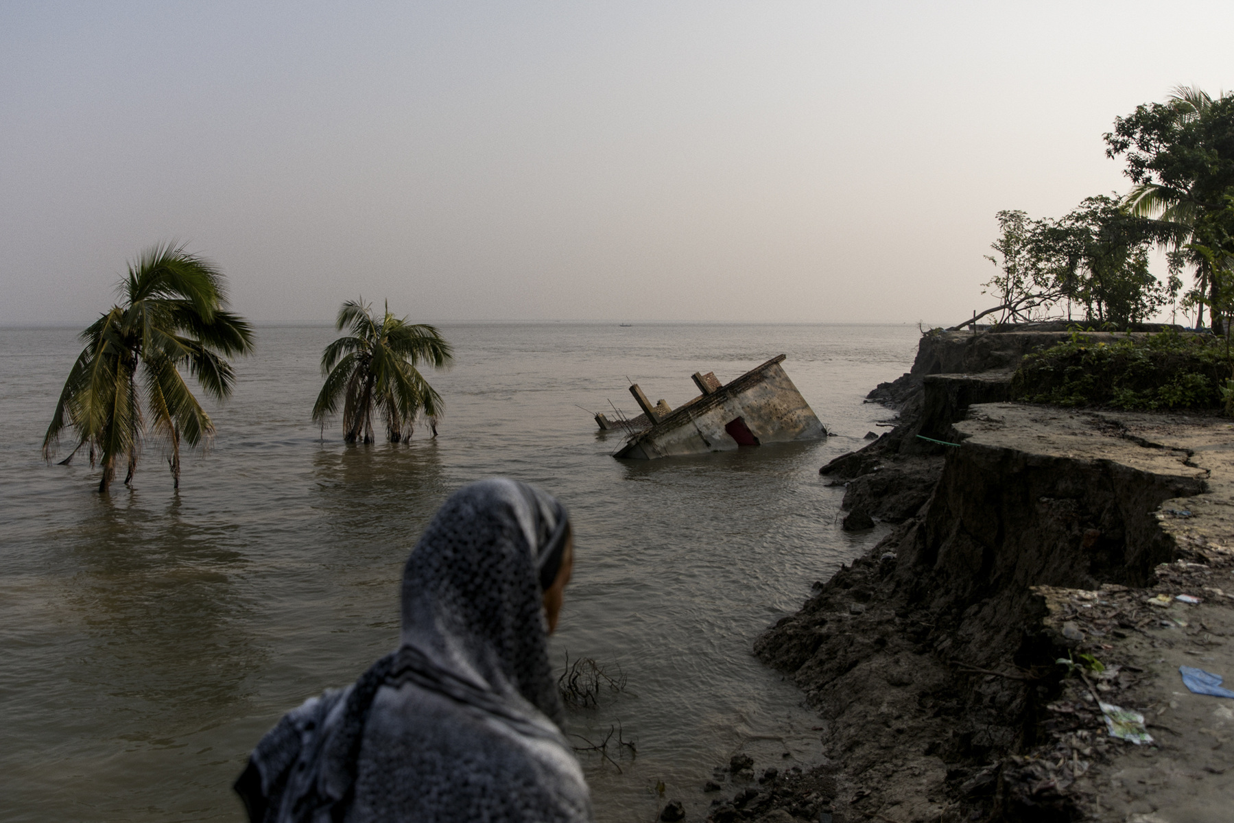 Adrienne Surprenant - 18/10/2018, Naria, Bangladesh — Bangladesh is the country in the world that is most impacted by climate change. The Prime Minister estimates that the country will struggle with 30 million climate migrants by 2050. In 2018, 2km2 of land disappeared in two months in the Padma river, leaving 4200 to 5000 homeless as of the September 15,2018, according to an ACAPS briefing note. Two health clinics and parts of a bazaar have also been destroyed because of the flooding. In the past seven years, 13 km2 of land fell into the Padma River. In the past seven years, 13km2 of land fell into this river, the biggest channel of the Ganges.