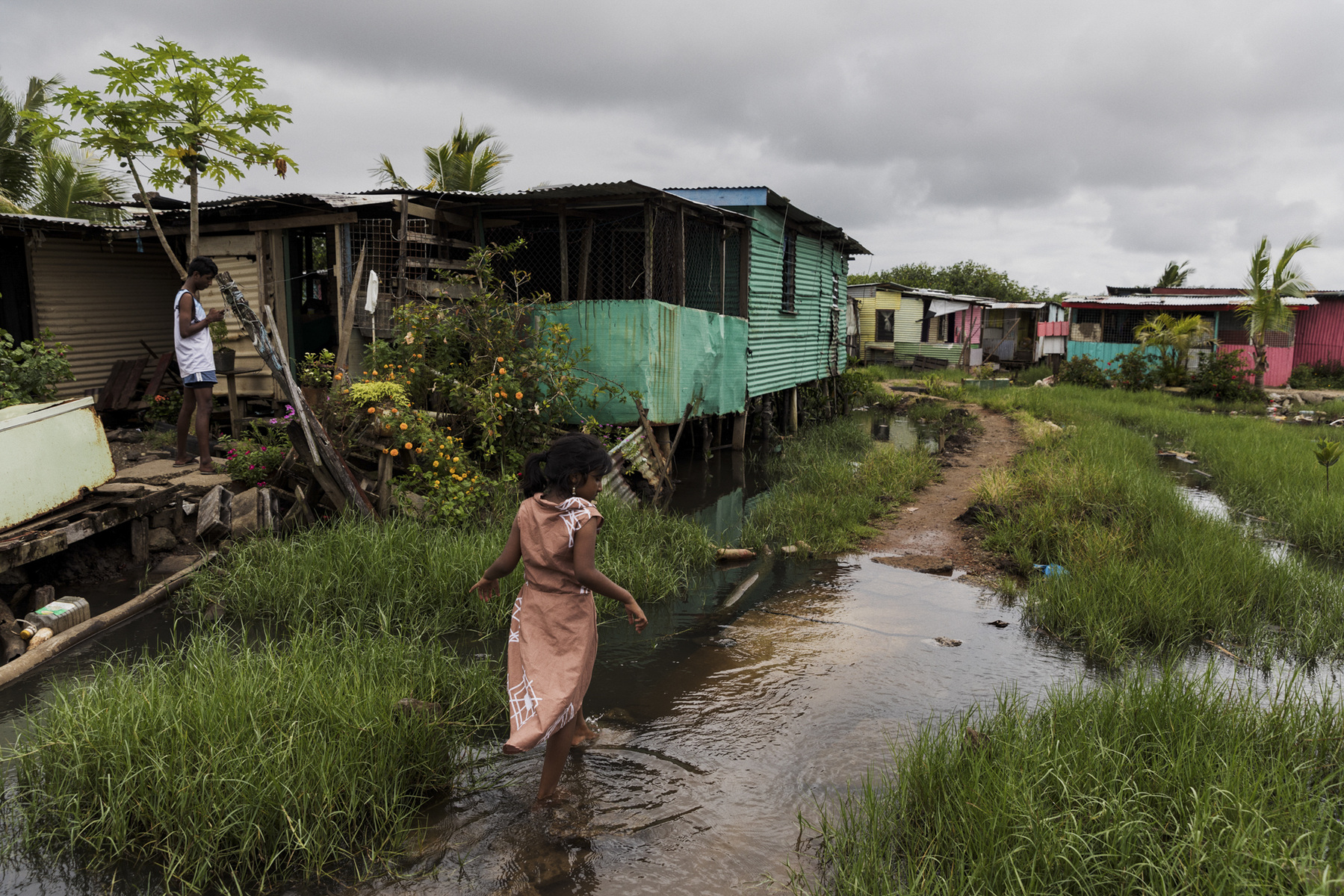 Adrienne Surprenant - 01/01/2019, Suva, Fiji—Shirya walks behind her house in the Nanuku settlement, during the rain and cyclones season. Shirya and her father Sunil both had dengue for the first time in August 2018. She was hospitalized for four days, but he was kept at the hospital for more than a week. I was very scared,  he recalls.