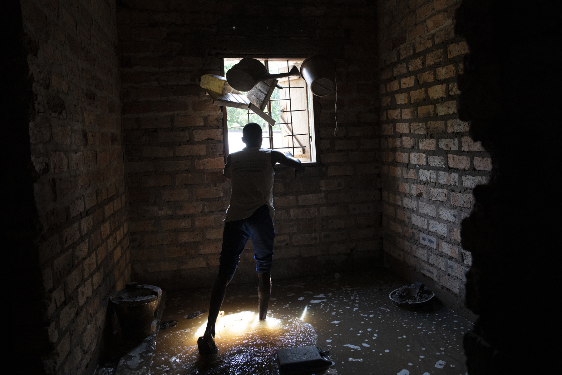 """Adrienne Surprenant - Paterne Kongbouali, 22-years-old, closes the window of a bedroom before leaving his family house. """"I feel as if it is the end of the world, I don't know,"""" he says. """"With that event, my family is dispersed, the young man have to stay near our house, the women left."""" November 5, 2019. Bimbo, the Central African Republic."""