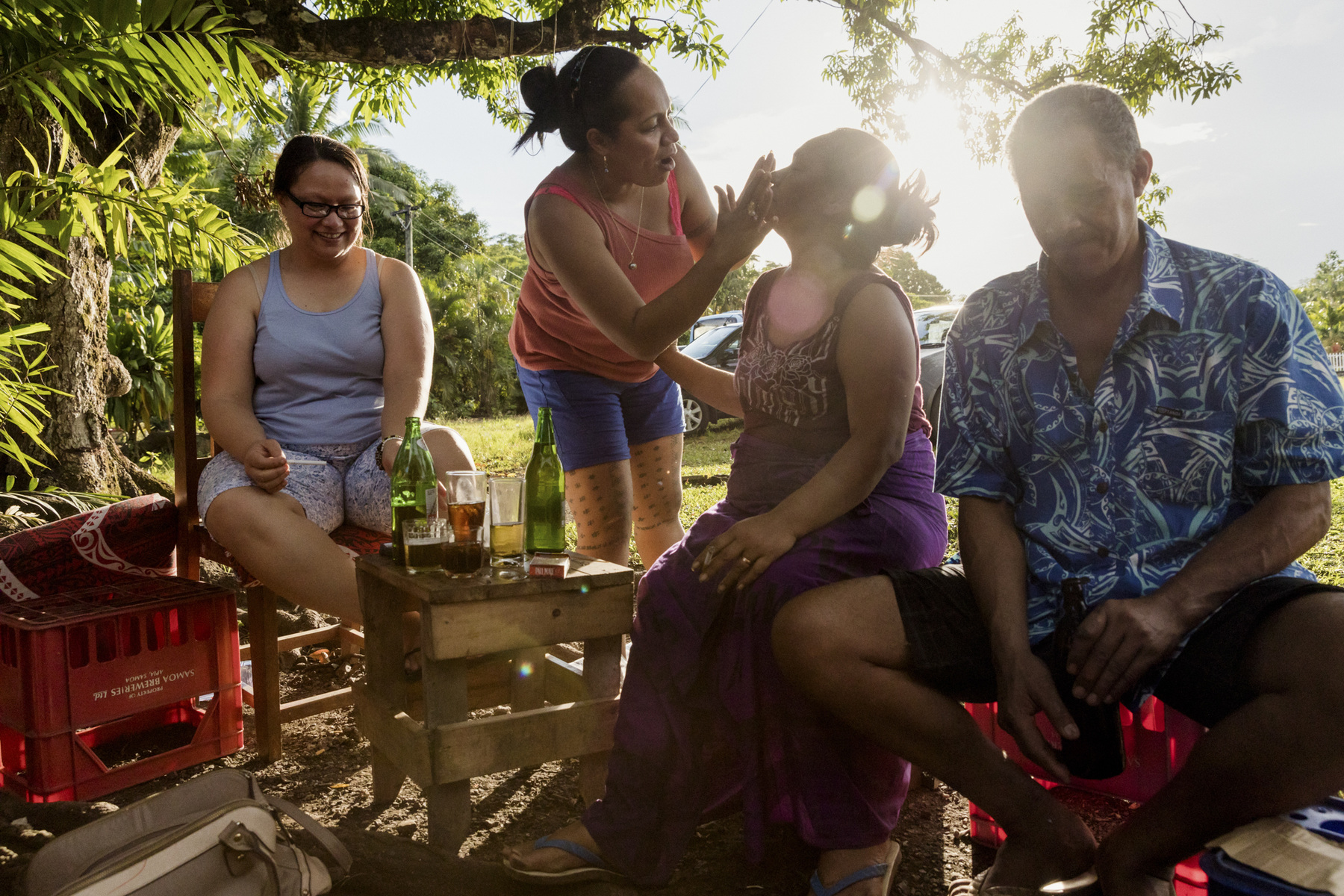 "Adrienne Surprenant - 23/12/2018, Apia, Samoa—""If 80% of people in Samoa had dengue once, it is that 80% of us like to drink beer outside,"" says a woman during her brother's 50th birthday, as a man lights a coil next to the party. All the family is reunited for the occasion, even the brothers and sisters living abroad in Australia or New Zealand. Their garden is filled with empty coconut shells and other mosquito breeding spots."