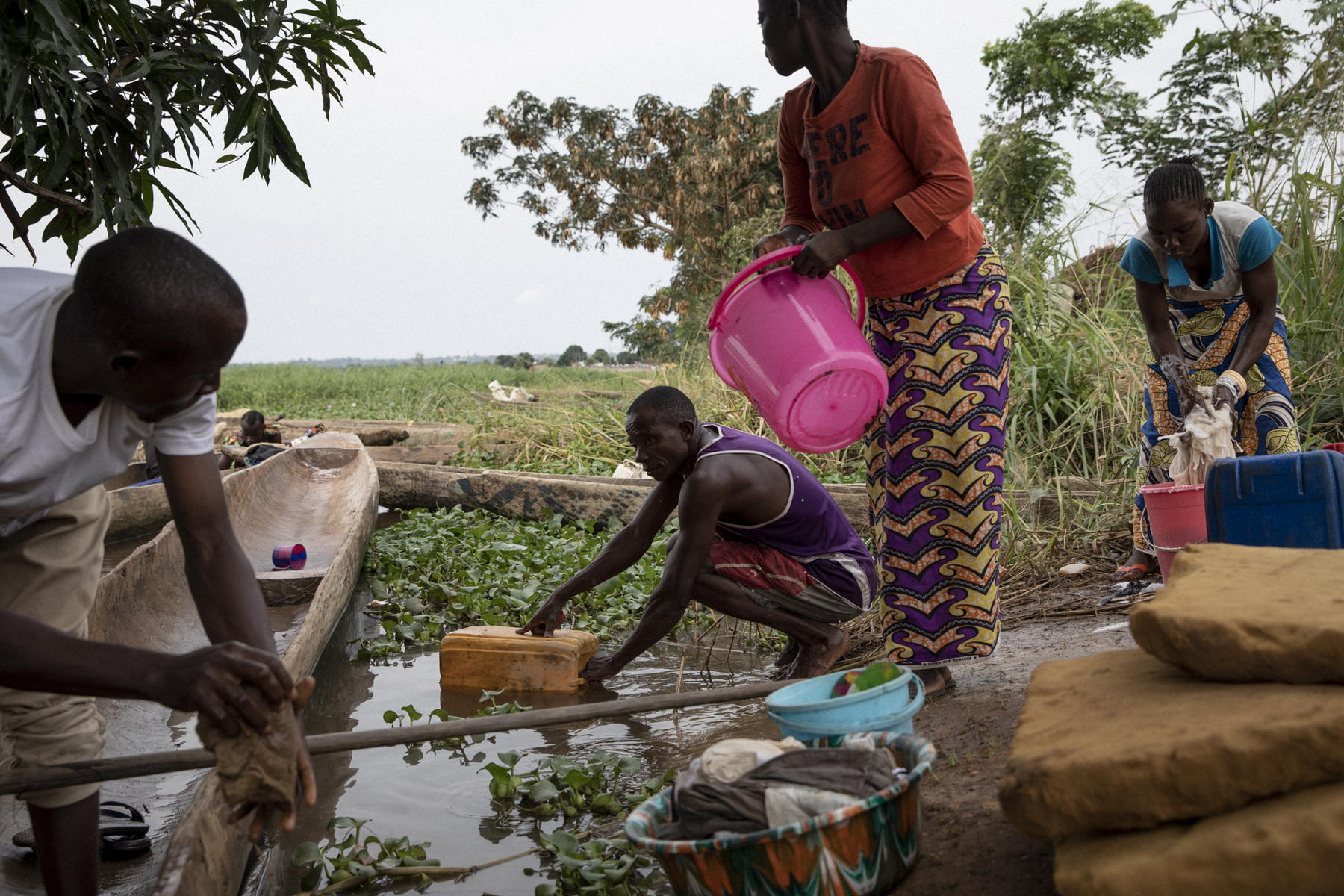 Adrienne Surprenant - Grâce à Dieu, the son of Île aux Singe's chief, is cleaning a boat next to people taking the Ubangi River's water to wash clothes and utensils. Twice a day, they receive a bucket of drinkable water. November 4, 2019. Bangui, the Central African Republic.