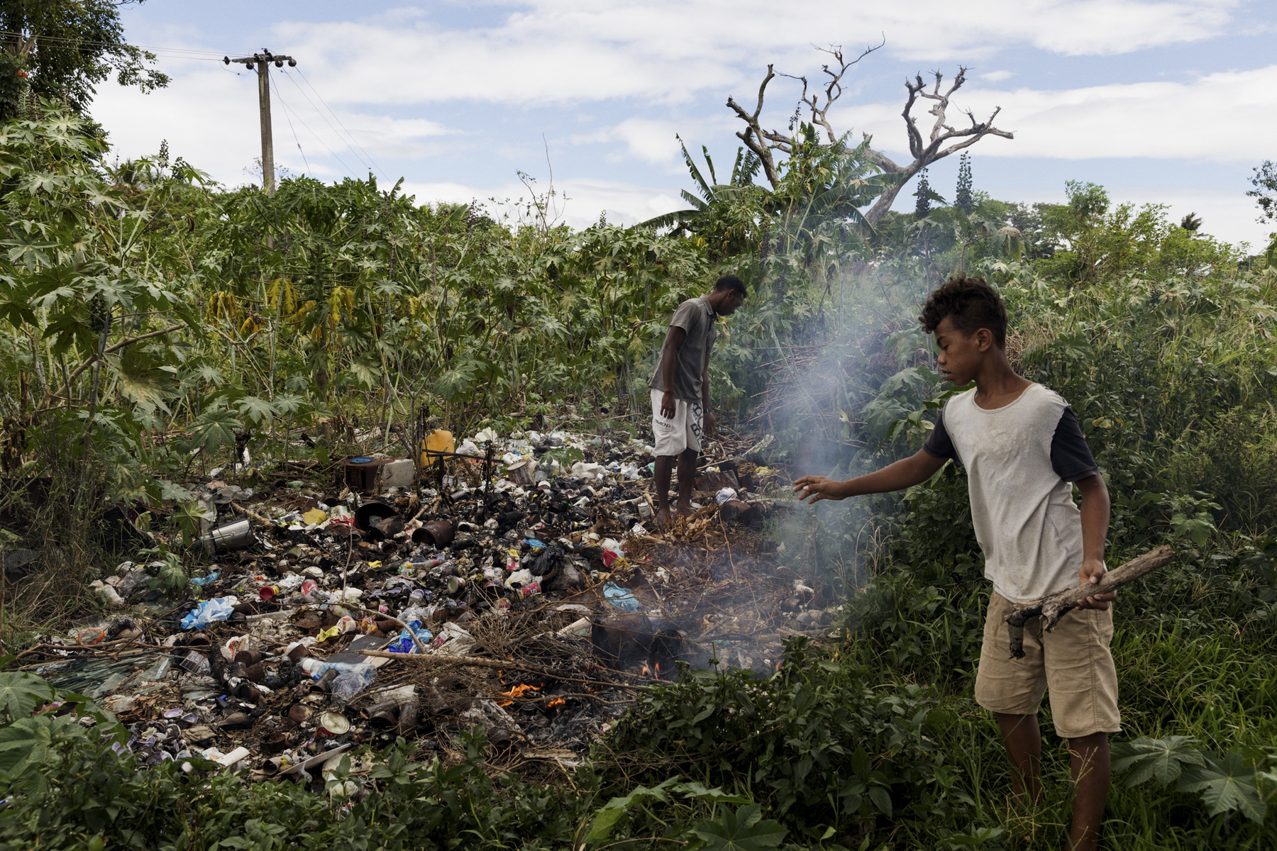 Adrienne Surprenant - 27/12/2018, Namotomoto (Nadi), Fiji—Ben and Paul burn garbage piles. In Namotomoto village, people have to bring their cans and garbage containing water in the middle of their fields, a couple hundred meters away. There, they used to bury them, but the field filled and the city workers never came to clean the dump. Three years ago, they started burning the piles of waste.