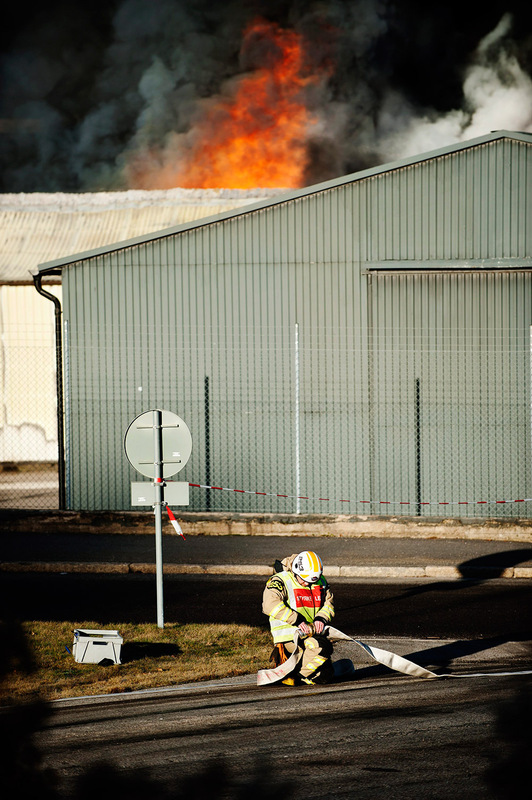Mareike Timm | Photo Journalist - A fireman fights with the hoses while high flames burst out from the workshop with car tires. For Borås Tidning, 2013.