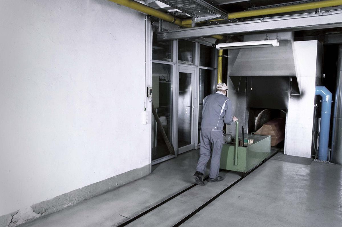 sebastiancunitz - Ein Mitarbeiter des Krematorium schiebt einen Sarg in den Ofen.