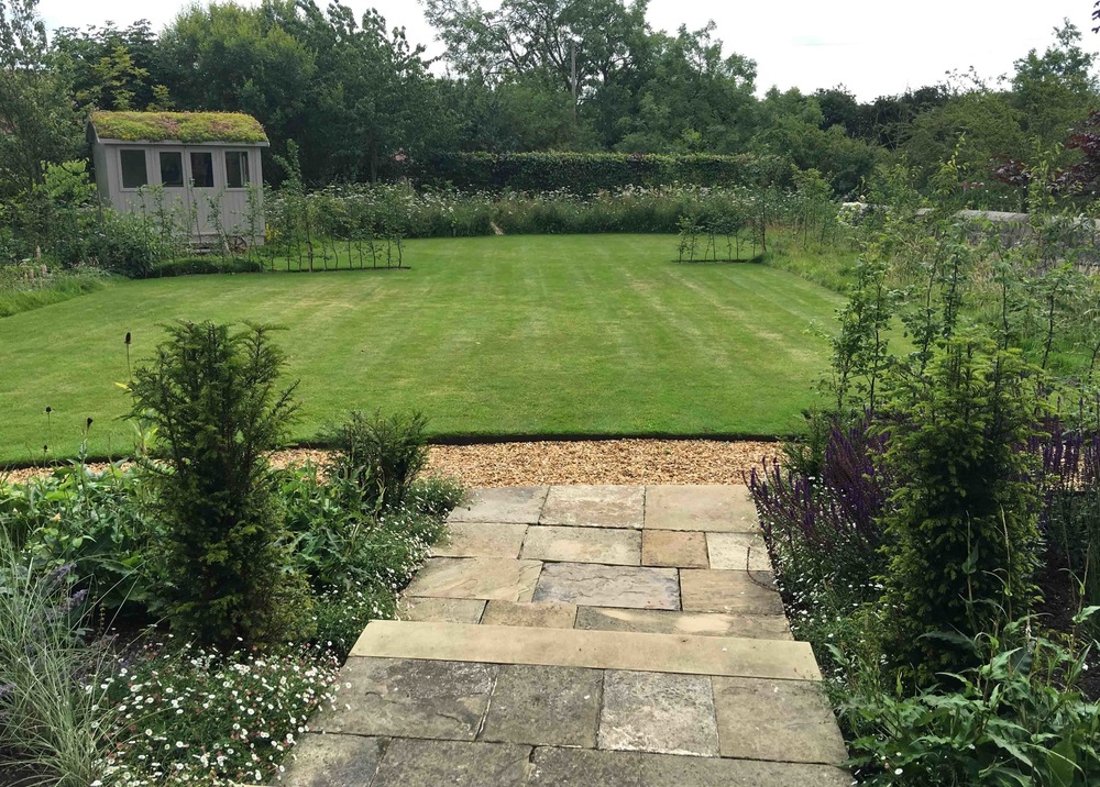 plants by design - The shallow york stone steps from the front door provide a vantage point to overlook the main garden. Yews in the foreground and hedges will be tightly clipped.