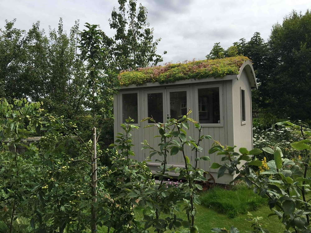plants by design - The summer room/caravan with a sedum roof provides a focal point and destination within the garden