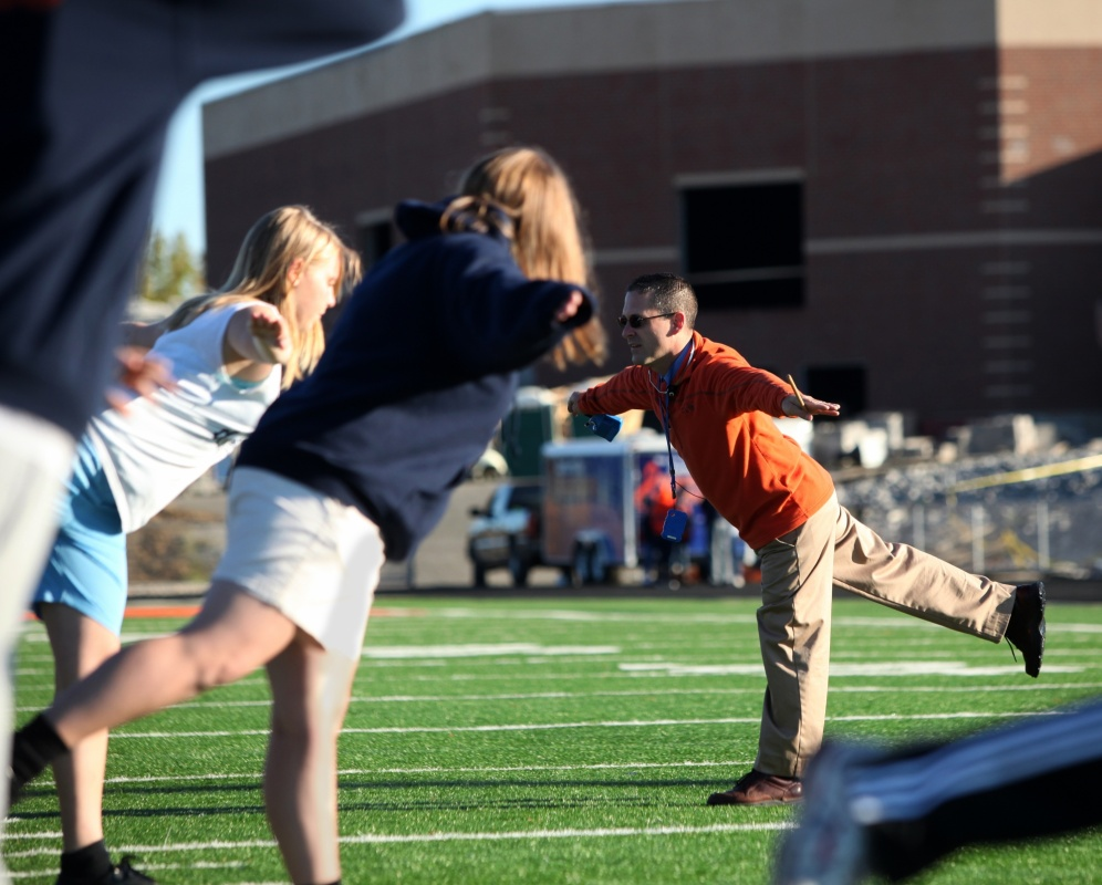 Jennifer Gonzalez | Multimedia Photojournalist - Todd Norrington demonstrates a balance exercise while having his band students stretch the morning before the Music In Motion band competition.