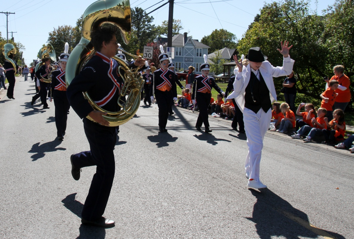 Jennifer Gonzalez | Multimedia Photojournalist - Senior Michael Frangello dances around sophomor co-drum major, Emily Weisel, as the Carterville Marching Lions march and perform down Division Street during the homecoming parade.