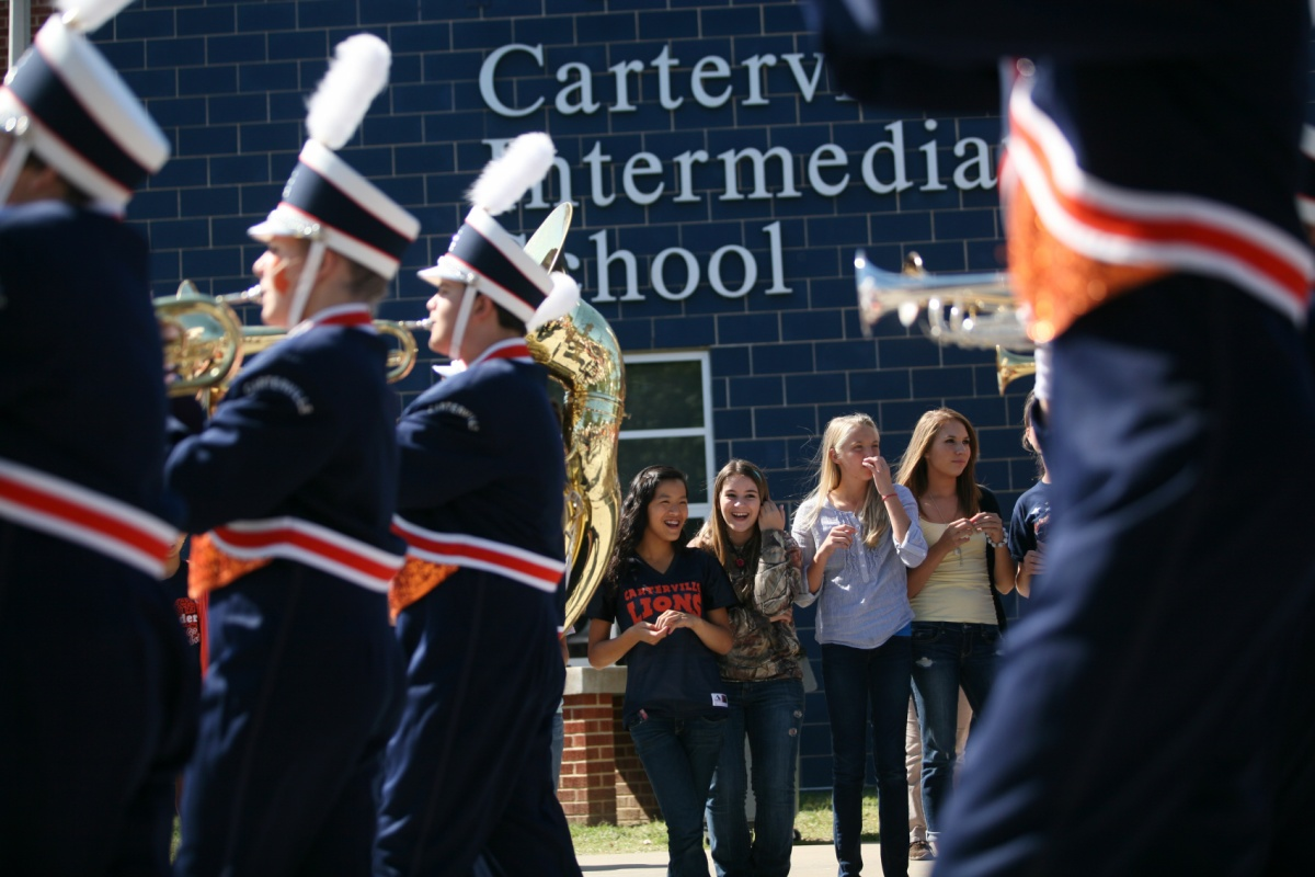 Jennifer Gonzalez | Multimedia Photojournalist - Carterville Middle School students laugh and dance as the Carterville Marching Lions pass in front of them during the homecoming parade.