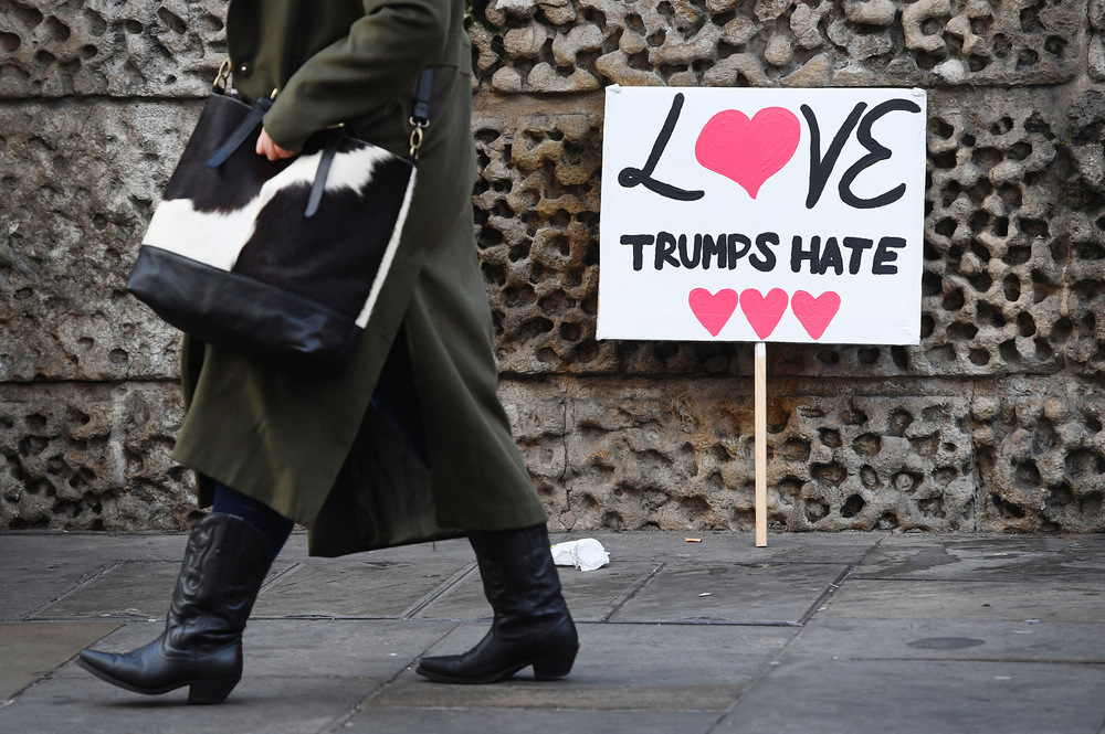Victoria Jones Press Association Photographer - January 2017  A woman walks past a protest banner against Donald Trumpin central London during a march to promote womens rights in the wake of the US election result.