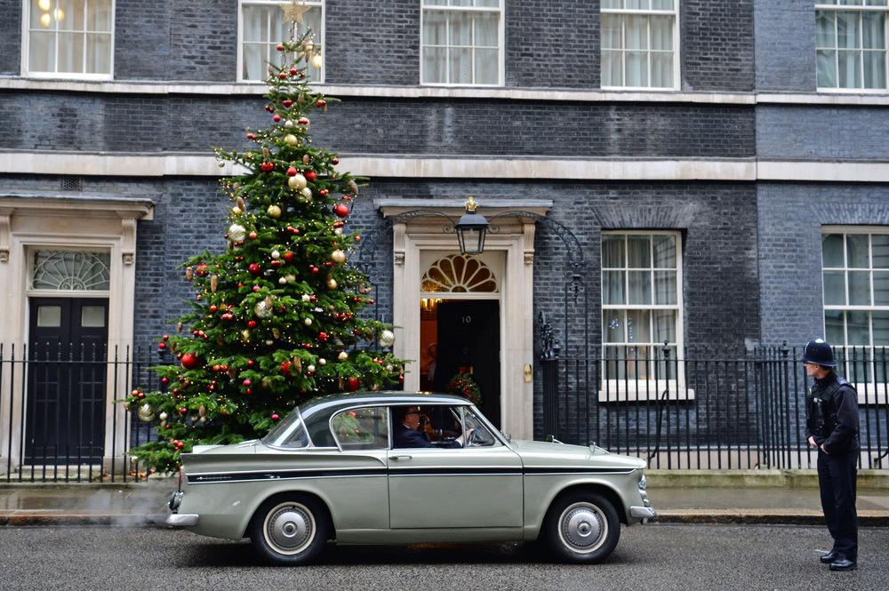 Victoria Jones Press Association Photographer - December 2017  A police officer looks at Greg Knight MP arriving in Downing Street, London, in a 1961 Sunbeam Rapier car.