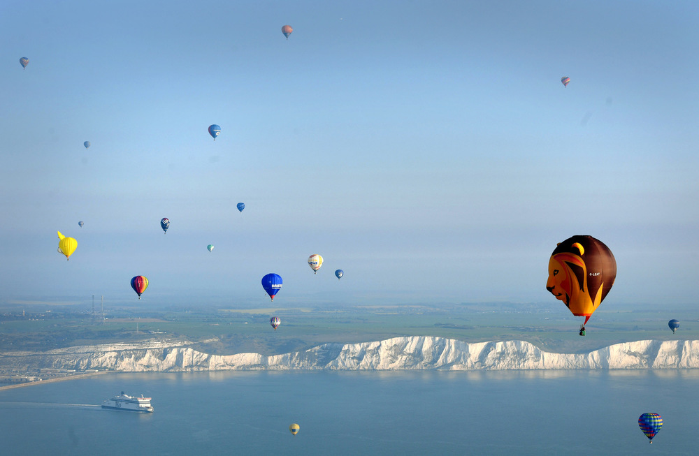 Victoria Jones Press Association Photographer - April 2017  Some of the 100 balloons taking part in a World Record attempt for a mass hot air balloon crossing of the English Channel, fly over the White Cliffs of Dover in Kent.