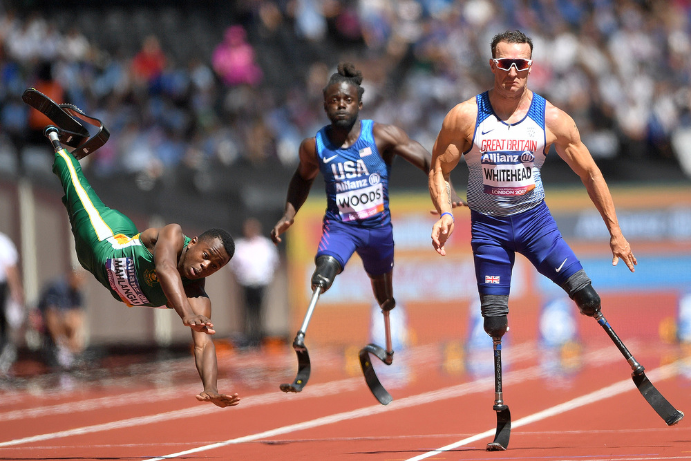 Victoria Jones Press Association Photographer - July 2017  South Africas Ntando Mahlangu trips in action as Great Britains Richard Whitehead (right) wins the Mens 100m T42 first heat during day four of the 2017 World Para Athletics Championships at London Stadium.