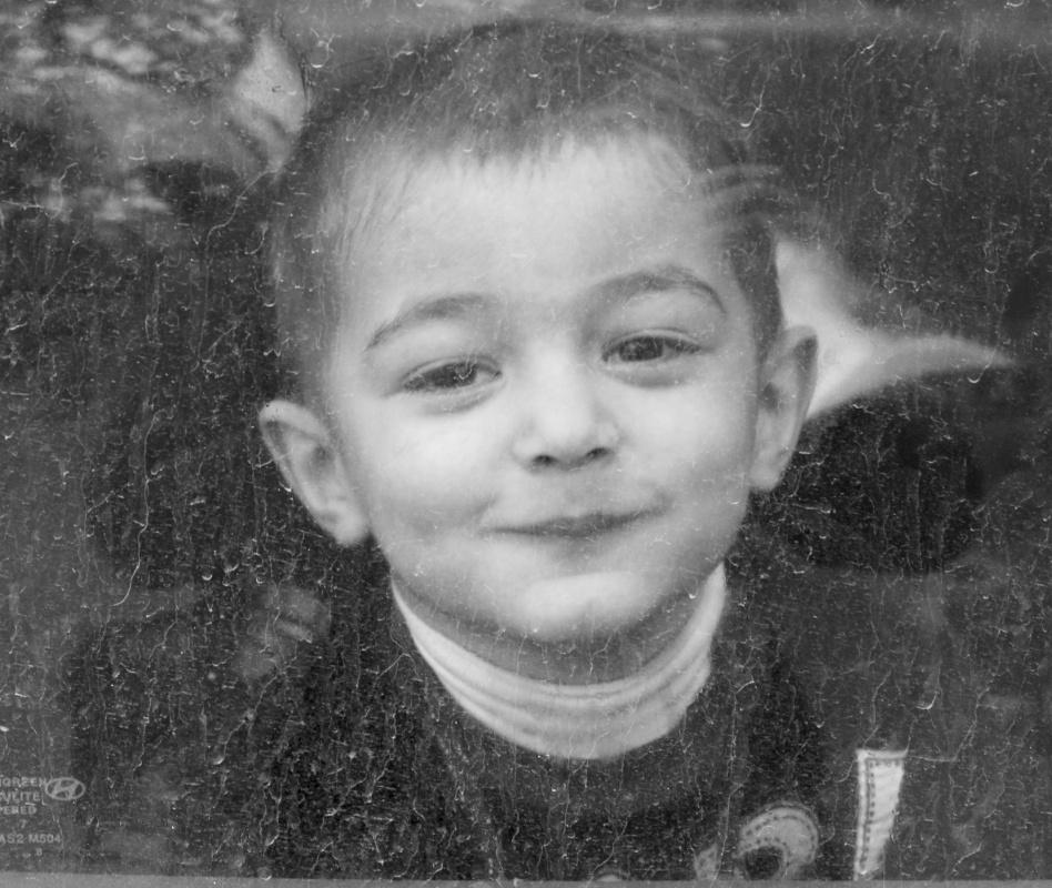 Tariq AlHadad - Kid behind dirtied car window, Baghdad, Iraq