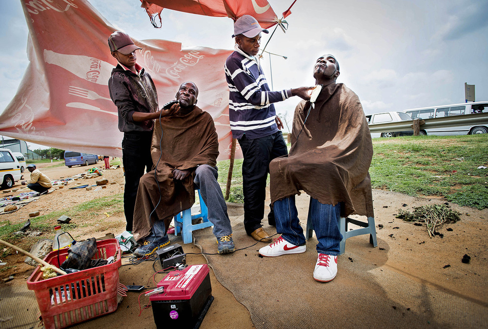 John T. Pedersen Photography - 2013 BARBERERS IN SOWETO  Take-Away barbers are using a car battery, two razors and cooking oil.Julio Ernest (17) and Dick Mgwenya (30) manage to survive. Bythe noisy main road into Soweto, two men sit and shave for a couple of dollars each.  Both hairdressers and customers are on alert. If the police show up, we just have to run. In the old days, we were kicked by the police and called donkey.  Today we are free thanks to Father Madiba.