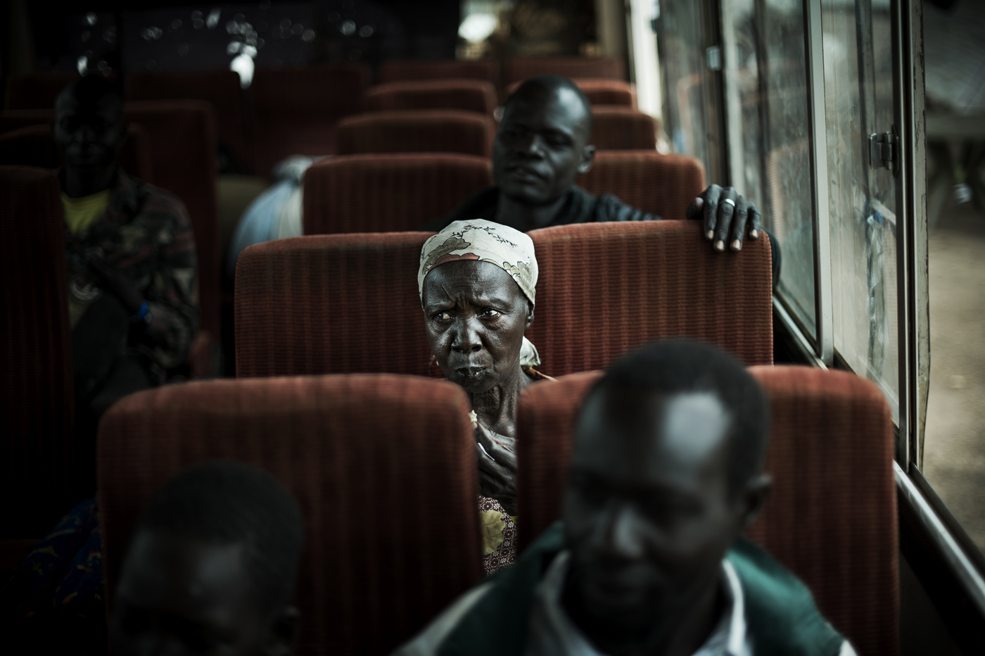 John T. Pedersen Photography - Buses transport the registered refugees from reception camps and on to the settlements. A single elderly woman is on her way.