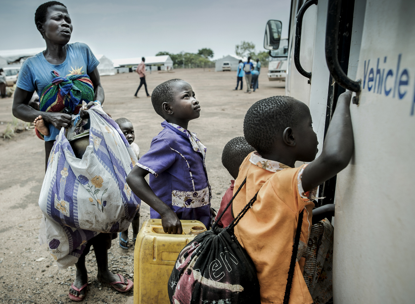 John T. Pedersen Photography - A mother with her children on their way with their belongings onto the bus that will take them further into BidiBidi. Many of the refugees only have what they are wearing.