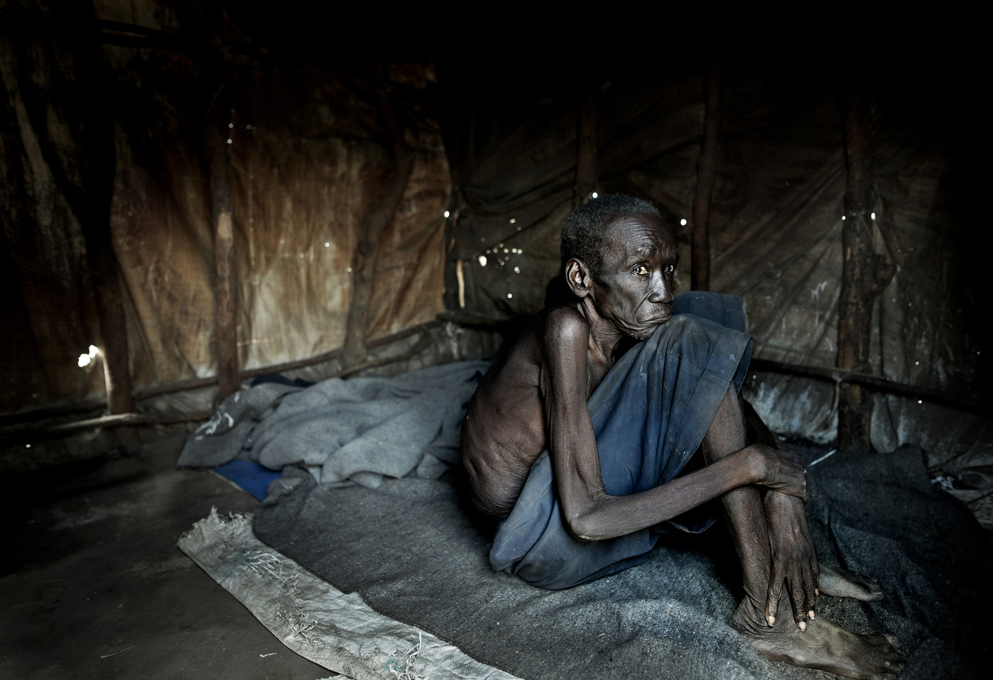 John T. Pedersen Photography - Sube Lokiri (76) sits mostly all day inside his tent. He is old and malnourished, and needs the help of the family to cope. He just wants to get back home to his village in South Sudan.