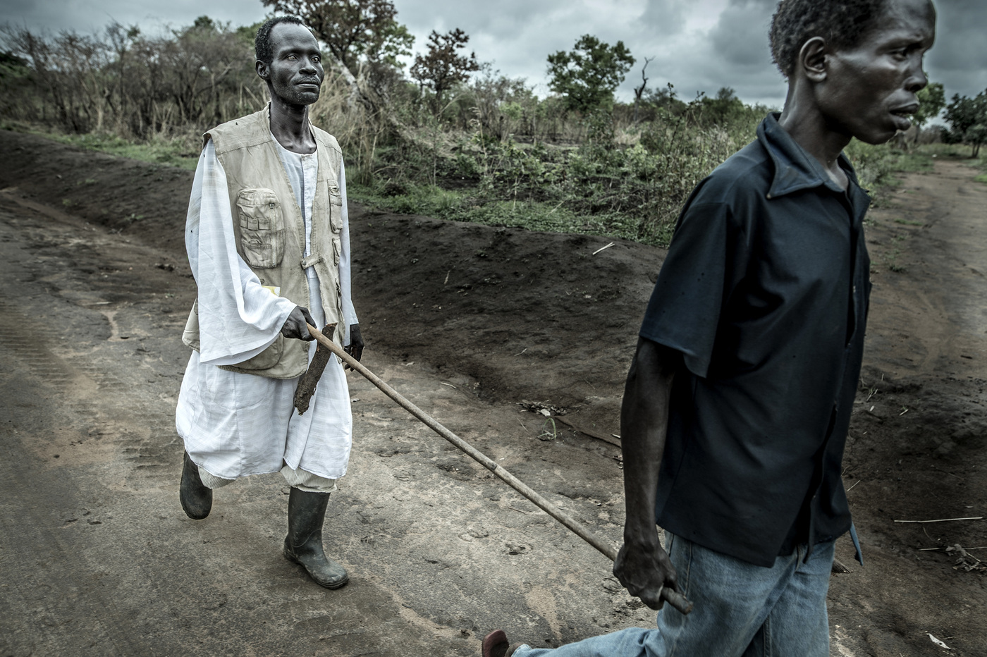 John T. Pedersen Photography - A blind man is guided by another mancrossing the border in the bush. Some walks for days and weeks to get from their village in southern Sudan and onto the Ugandan side.