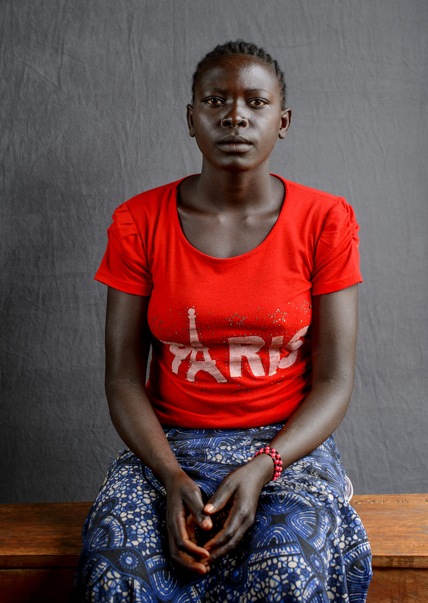 John T. Pedersen Photography - Florence Awate (18)   My husband was slaughtered by the government soldiers outside the house of my family. I witnessed it myself.   Then two soldiers raped me    I escaped afterwards. I will never return to South Sudan. My hope is to start studying here in Uganda.   Florence walked seven days with her one child from the village of Yei.