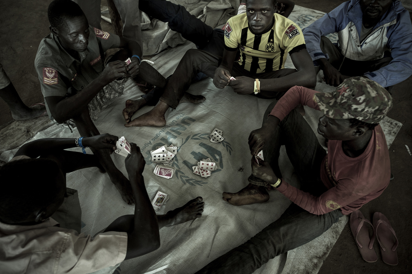 John T. Pedersen Photography - A maximum of 48 hours takes the time to be registered by the authorities, and a residence permit can be granted. Some find common knowledge on the Ugandan side.  Some guys play cards while waiting while waiting for further transport to the settlement area.